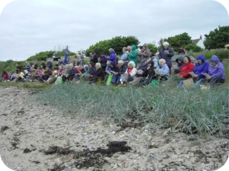 photo of hardy pilgrims praying on the beach