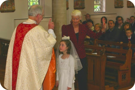 photo of Father White giving First Holy Communion to a girl