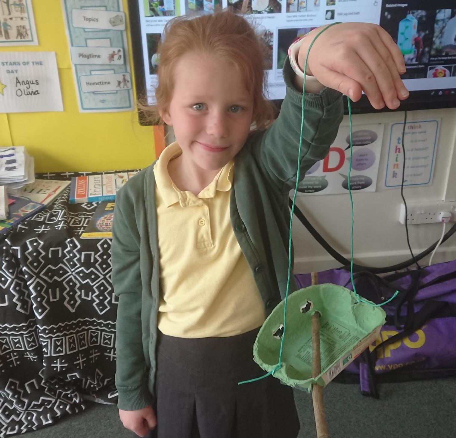 A Year 3 pupil at St John of Beverley with one of the bird feeders the school has placed around its grounds