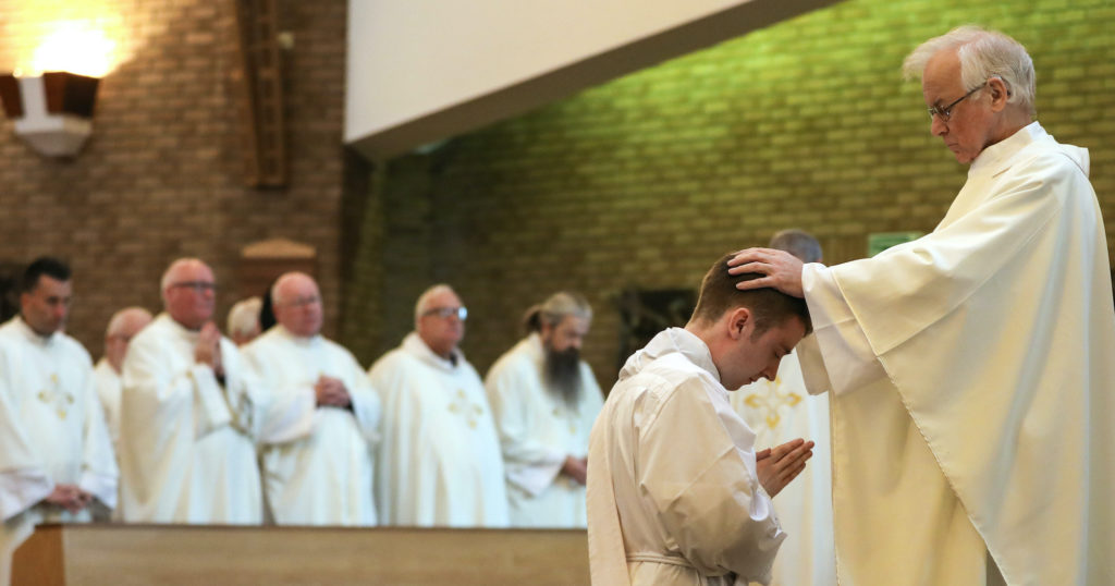 Father John Wood laying hands on the newly ordained Father Peter Taylor at St Mary's Cathedral in September 2019 – Photo by Chris Booth